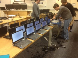 Seniors and members of the 1:1 Student Help Desk Andrew Lobos, Nick Joniec, Collin Enders and Aaron Jandzio (left to right) set up a new batch of 1:1 computers.